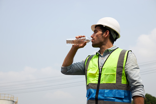 A male construction worker in protective clothing and a helmet, drinking water to quench his thirst in the harsh sunlight.