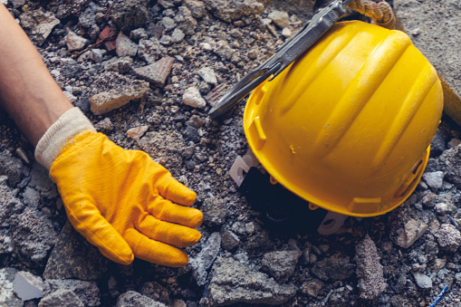 A worker's arm is shown lying next to a yellow hard hat on the ground