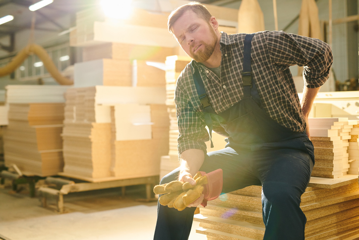 Warehouse worker sits on a stack of wooden boards while experiencing back pain