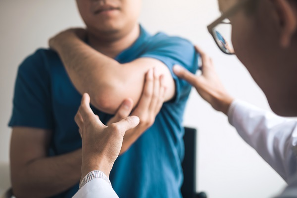 Doctor checking patients elbow office room.