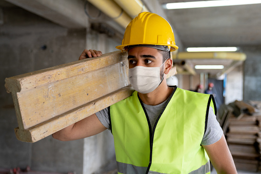 Portrait of a Latin American contractor wearing a facemask while working at a construction site carrying wood during the COVID-19 pandemic